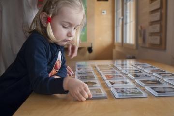 Mädchen spielt Memory - Fachartikel Schenken aber fair - Stiftung Kinderdorf Pestalozzi